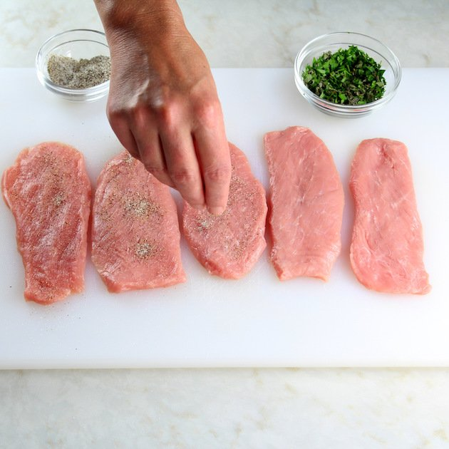 seasoning cutlets of veal on a cutting board