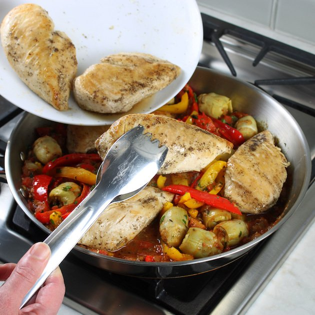 adding cooked chicken breasts to skillet with artichoke hearts and bell peppers