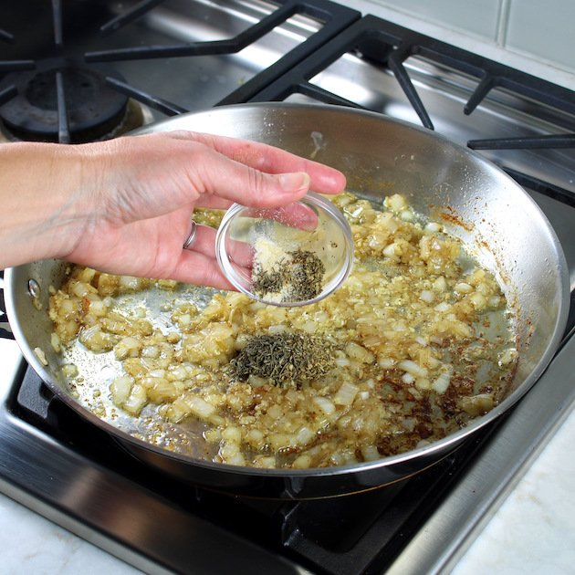 adding herb to saute pan with onions