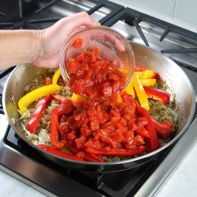 adding diced tomatoes to skillet