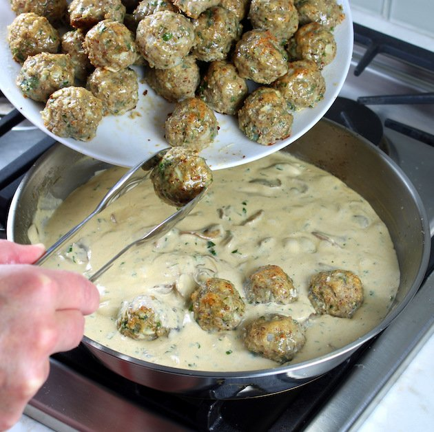 Adding cooked meatballs to the creamy parmesan mushroom sauce