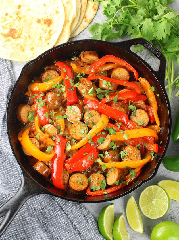 Cast iron skillet with bell peppers and sliced chicken sausage