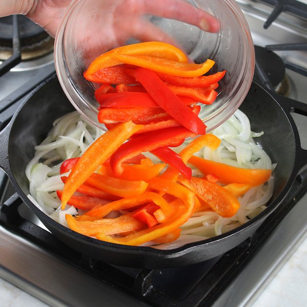 adding sliced bell peppers to skillet of onions