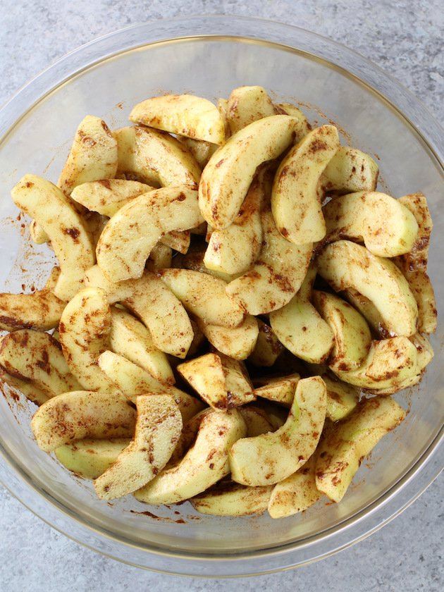 Bowl of peeled & sliced granny smith apples tossed in cinnamon