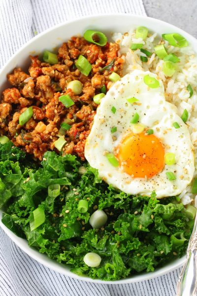Fried egg in bowl with spicy Korean chicken meat, kale, and rice