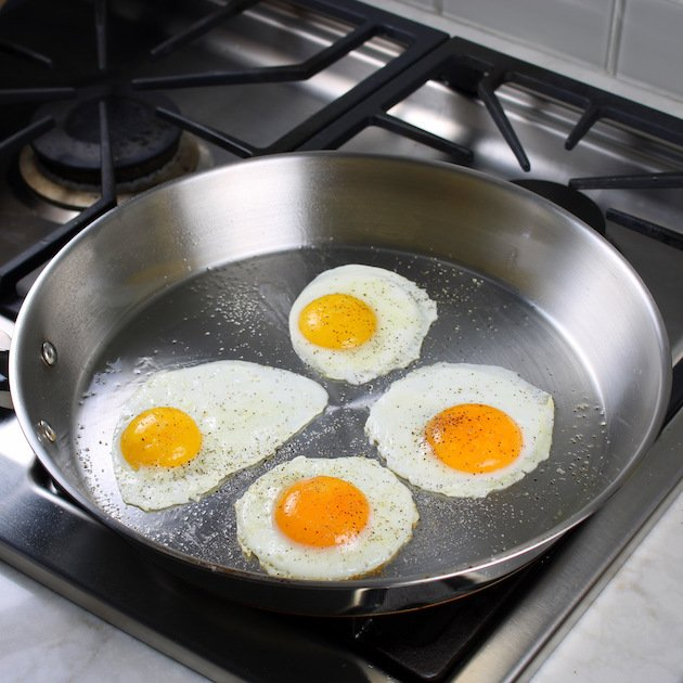 4 eggs frying in silver saute pan