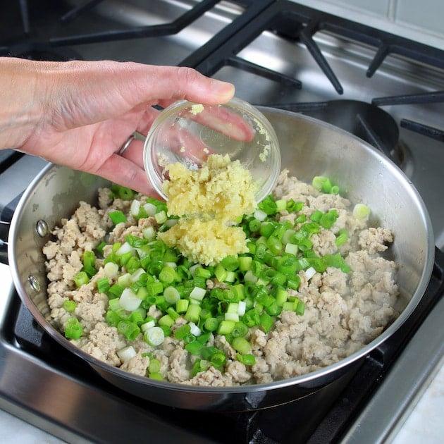 Adding shredded ginger to saute pan