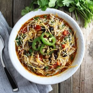 bowl of chili topped with shredded cheese and jalapenos