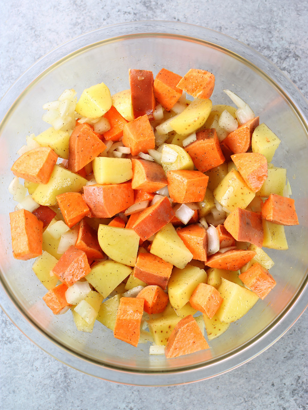 Large glass mixing bowl with chopped root vegetables