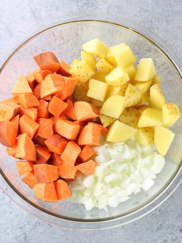 Sweet potatoes and yukon gold potatoes chopped in large mixing bowl