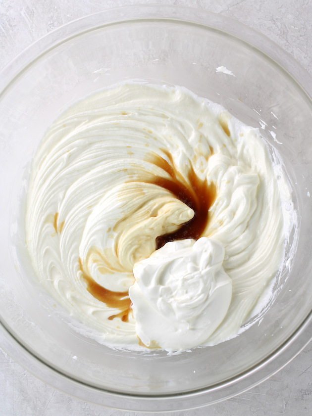 adding vanilla extract to whipped cream cheese mixture in a glass bowl