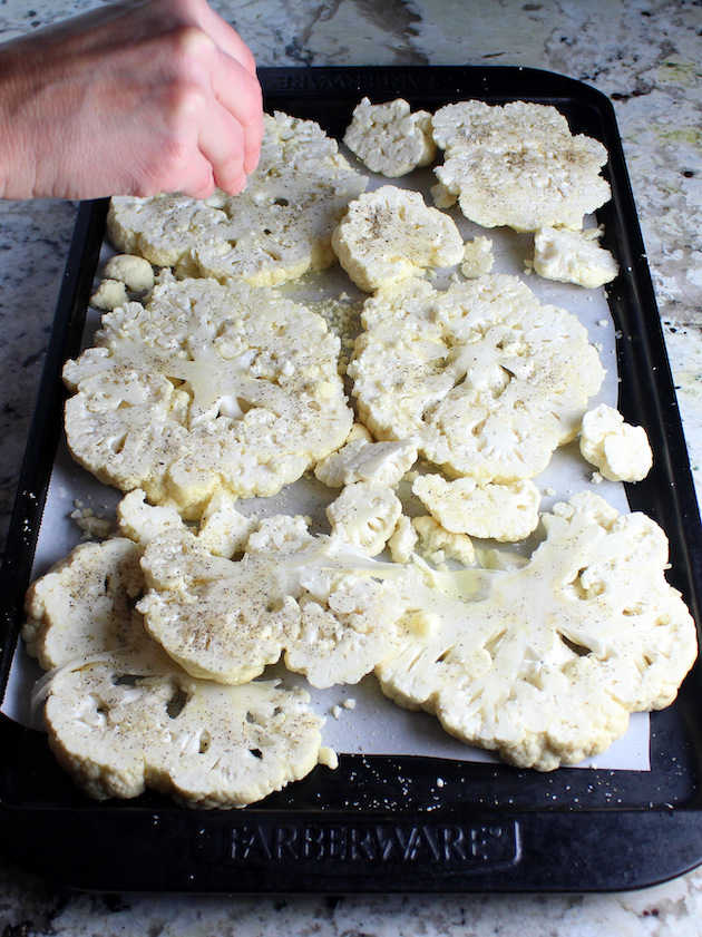 Adding salt and pepper to sliced cauliflower steaks on baking sheet