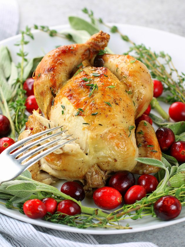 Cornish game hen on plate with sage and cranberries