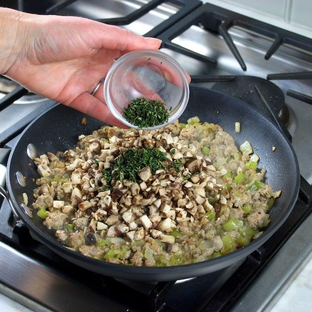 Adding herbs to saute pan