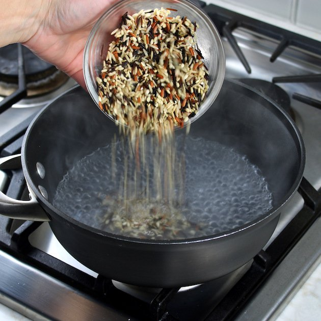 Adding wild rice to deep pot with boiling water
