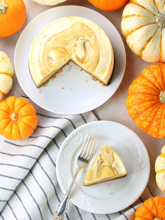 Pumpkin cheesecake on a plate with fall harvest squash