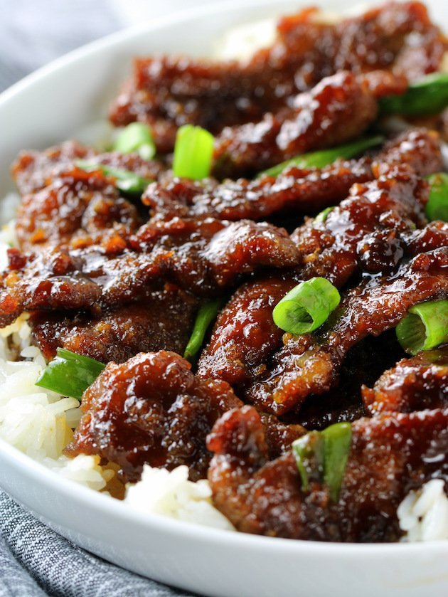 A close up of a plate of food with broccoli, with Mongolian beef