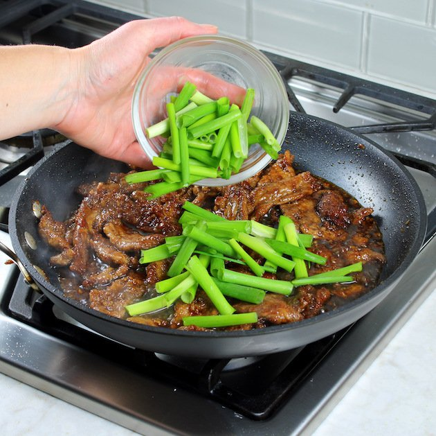 Adding green onions to a pan filled with meat and vegetables