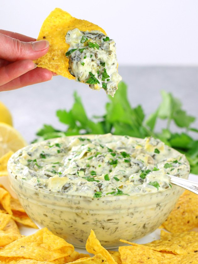 Hand holding corn chip with artichoke dip