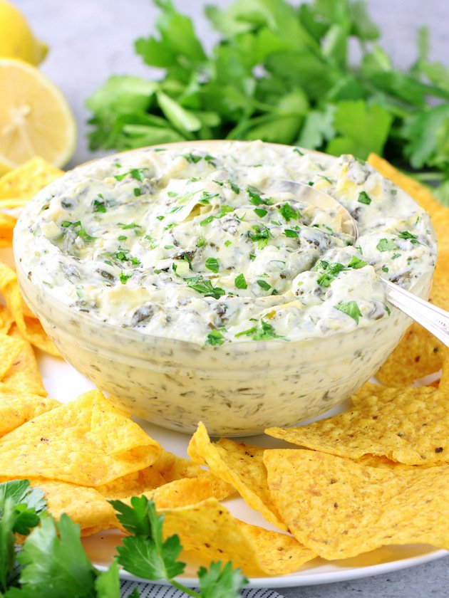 A bowl of artichoke spinach dip on a platter