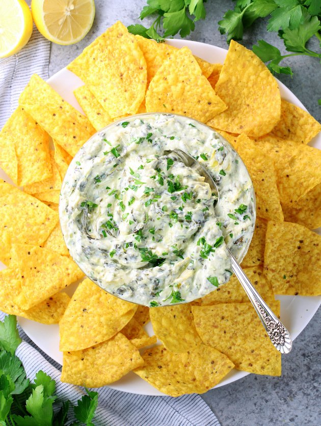 Bowl of spinach artichoke dip on plate full of corn chips.