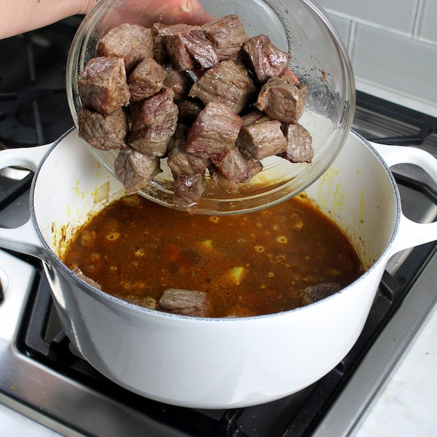 Adding seared cubes of beef into a large white soup pot