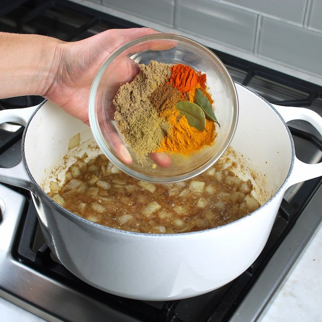 Adding colorful indian spices to large white soup pot