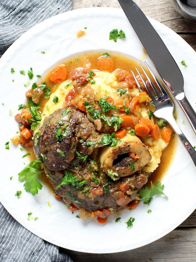 Cooked Veal Osso Buco veal shank on parmesan polenta with cooked carrots and gravy