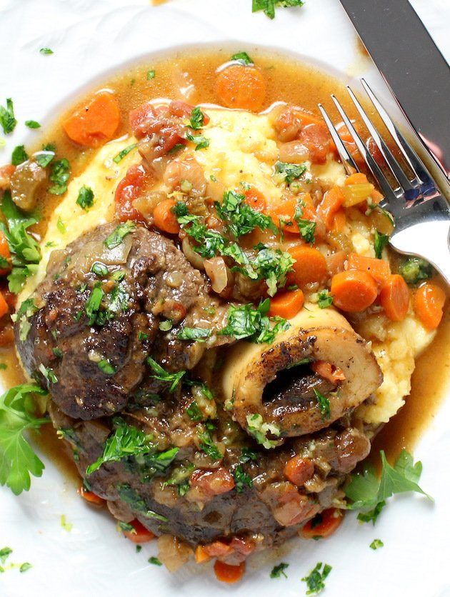 Veal osso buco on parmesan polenta with sauce and parsley garnish