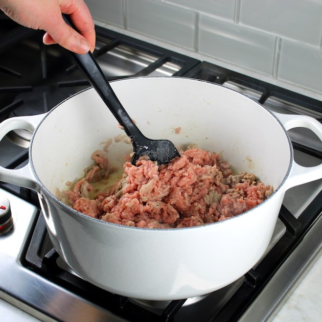 Cooking ground meat in large white soup pot on stove top