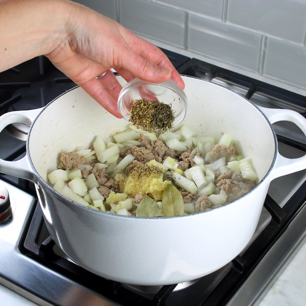 Adding spices to onions and meat cooking in large white pot