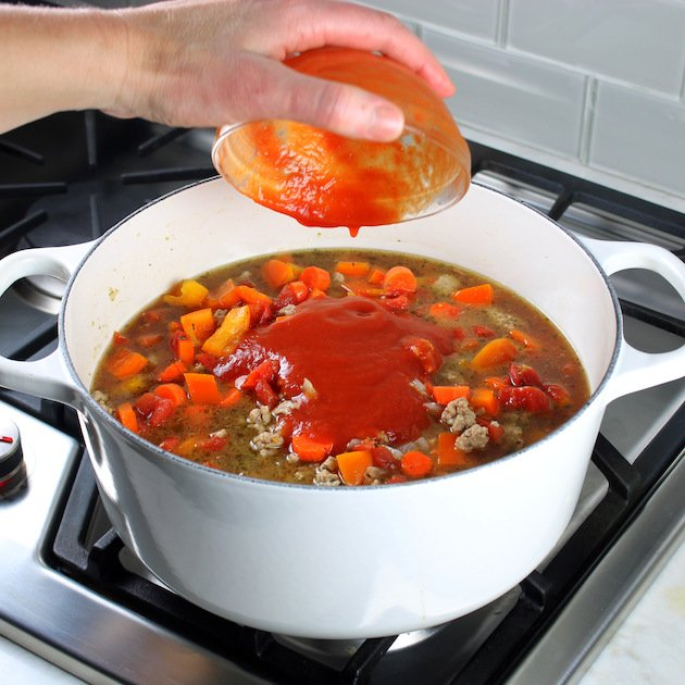 Adding ingredients to cabbage soup