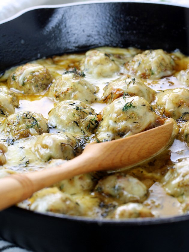 Eye level meatballs in a skillet covered with melted cheese