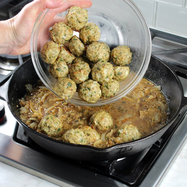 Adding baked meatballs to skillet with sauce