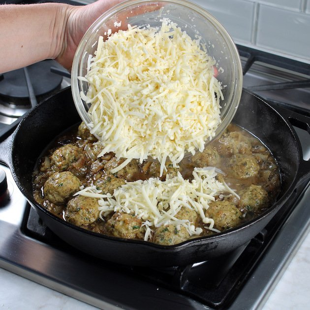 Adding shredded cheese to skillet full of chicken meatballs on stovetop