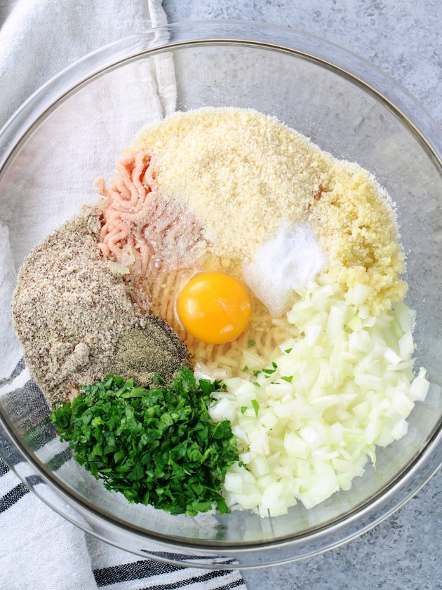 Large glass mixing bowl with ingredients for chicken meatballs before combining