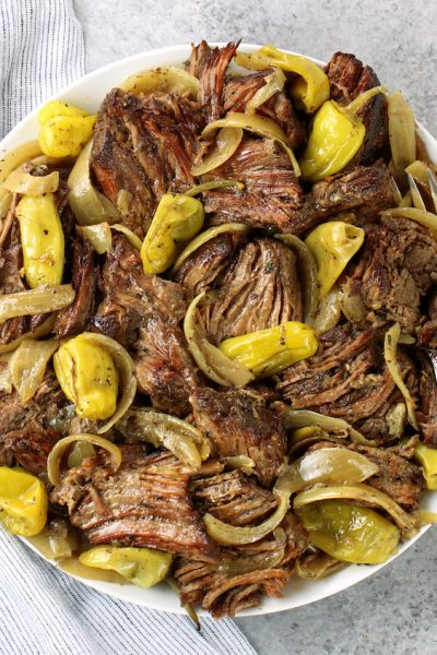 platter of pulled slow cooker Italian beef with onions and pepperoncini