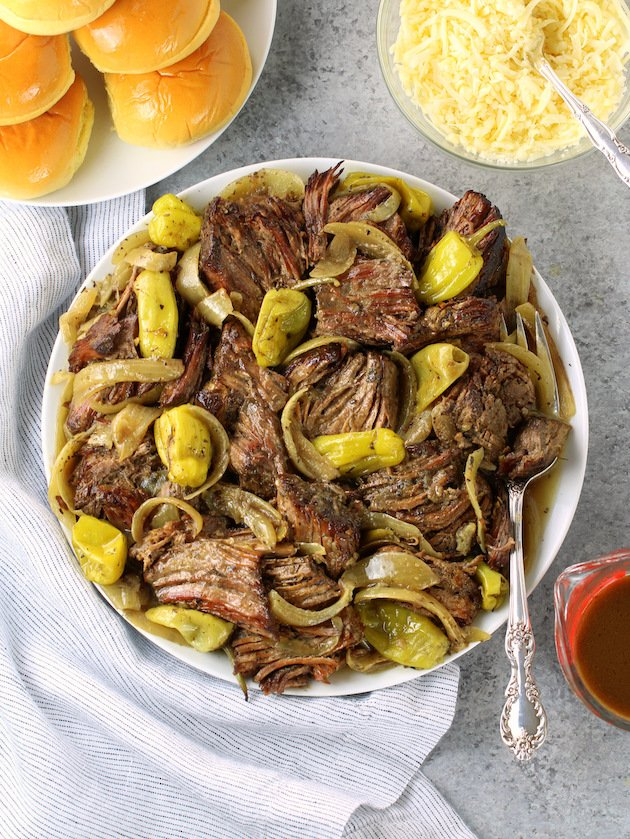 Platter of Italian beef with onions and pepperoncini on a table with buns and cheese