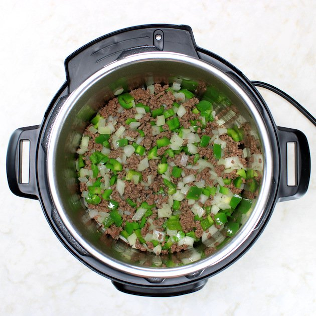 Onions and green peppers cooking in instant pot with ground beef