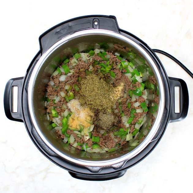 Herbs with Onions and green peppers cooking in instant pot with ground beef