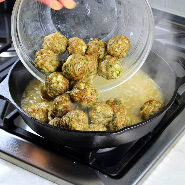 adding meatballs to saute pan with sauce