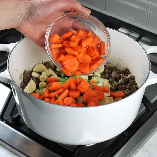 adding chopped carrots to pot of beef soup