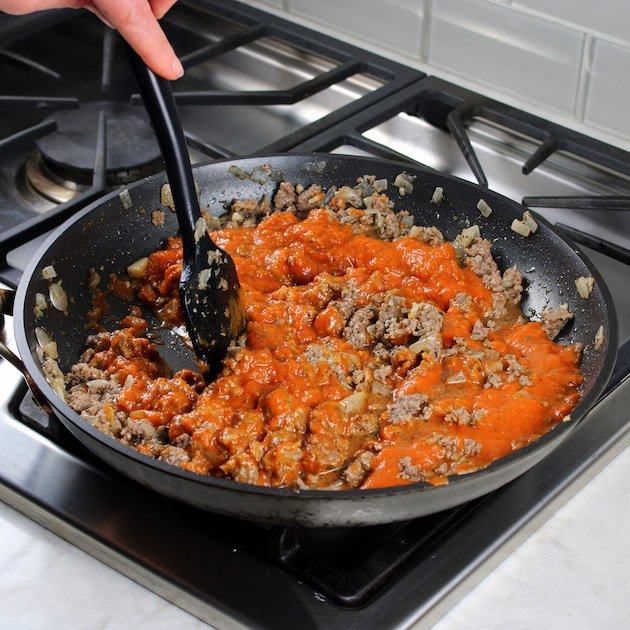 Ground meat cooking in skillet with red sauce