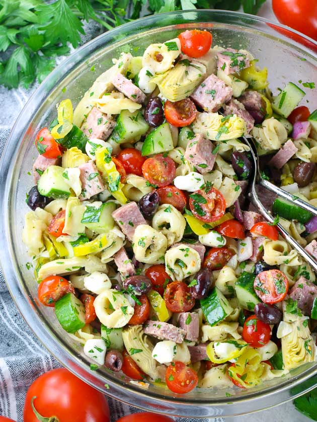 A partial bowl of salad with Tortellini, veggies, and olives.