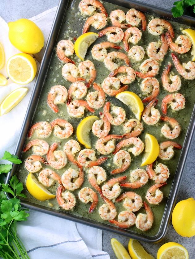 Easy Sheet Pan Lemon Pepper Shrimp cooked on baking sheet with lemon wedges.