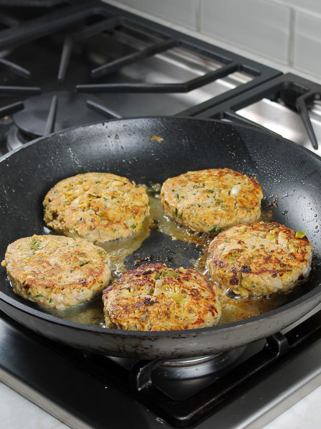 Buffalo chicken burgers cooking in a pan on the stove top