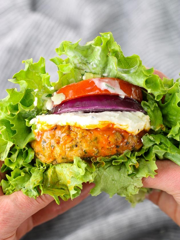 A close up of buffalo chicken burger with tomato and onion in a lettuce wrap