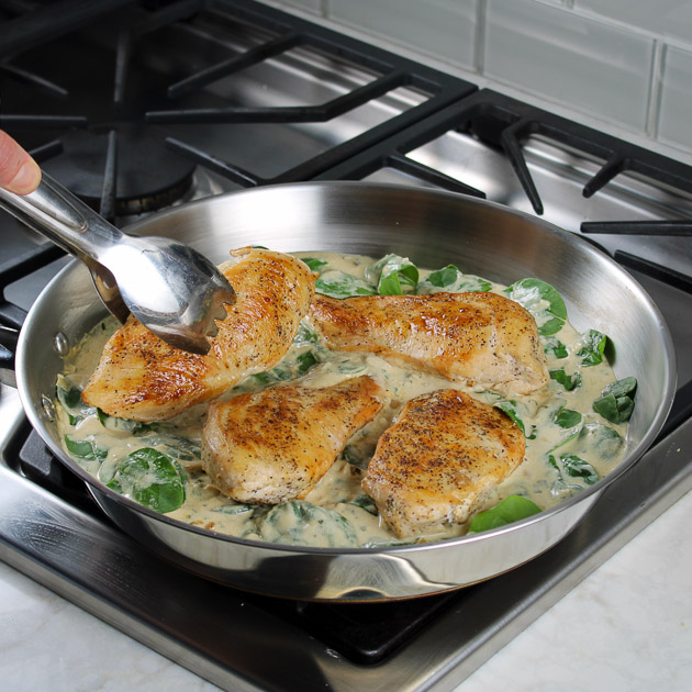 Chicken Florentine cooking in sauce on stovetop