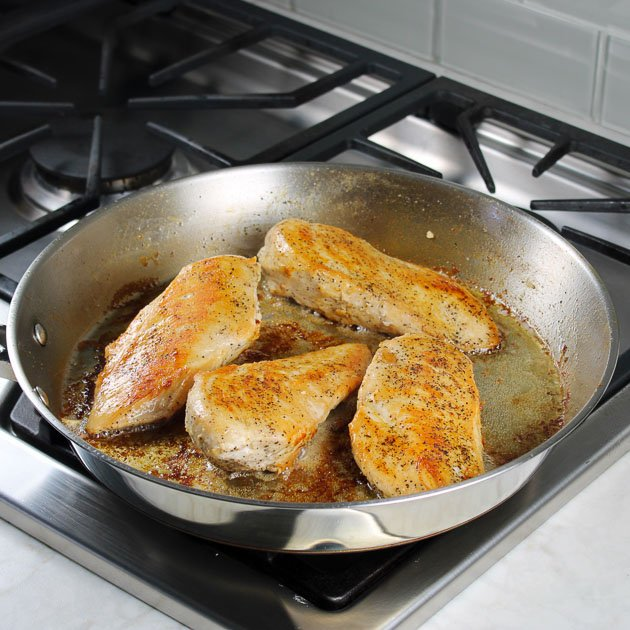 How to cook chicken in an skillet - 4 pieces of chicken cooking on stovetop