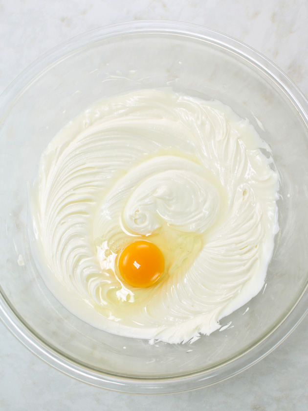 Egg added to whipped cheesecake mixture in glass bowl